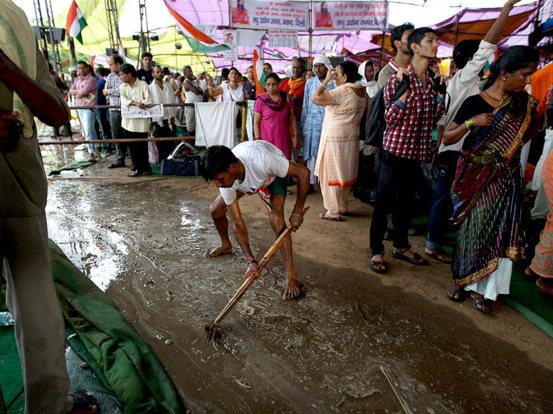 A volunteer creates a temporary passage for the rain water to flow after a heavy shower during the third day of Baba Ramdev's agitation against corruption and black money at Ramlila Maidan in New Delhi. PTI Photo/Vijay Kumar Joshi