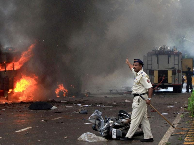 A policeman near a torched vehicle after a protest against Assam riots turned violent in Mumbai.(PTI/Shashak Parade)