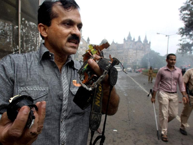 A photojournalist shows his broken camera after a protest against Assam riots turned violent in Mumbai. (PTI/Mitesh Bhuvad)