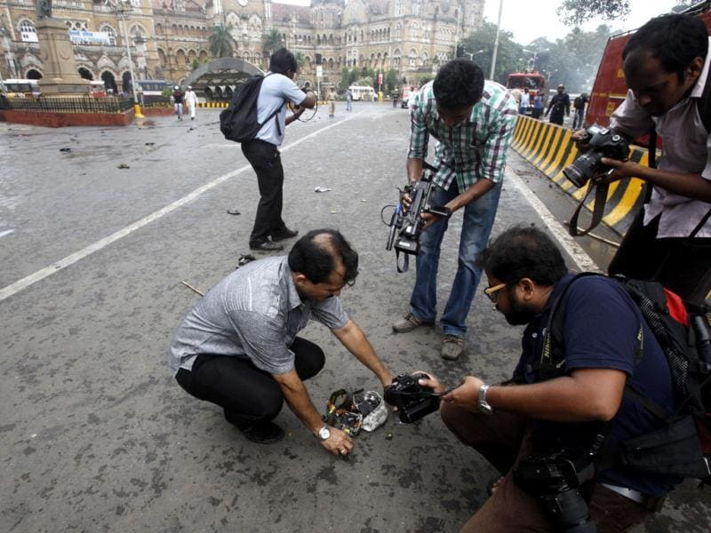 Media persons collect pieces of their cameras which got smashed in the scuffle betweeen protesters and police during the protest against Muslim killings Assam at Azad Maidan in Mumbai, India.(HT/Anshuman Poyrekar)