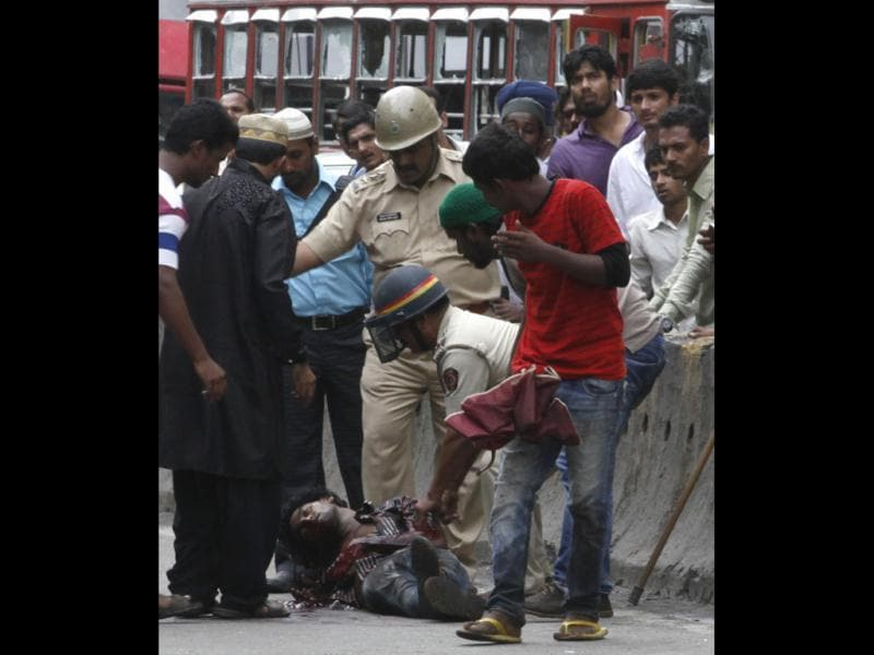 Police check on an injured person after the mob become violent during the protest against Muslim killings Assam at Azad Maidan in Mumbai, India.(HT/Anshuman Poyrekar)