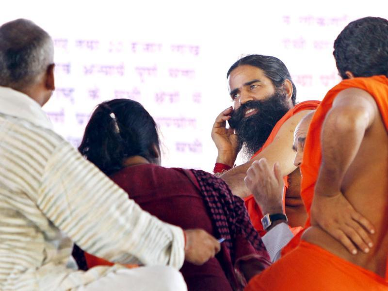 Yoga guru Baba Ramdev talks on mobile during the strategic meeting with his followers on third day of agitation against Corruption and black money at Ramleela maidan in New Delhi. HT Photo/Mohd Zakir
