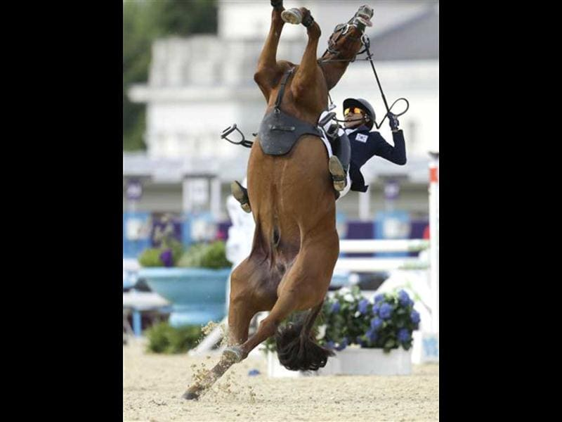 Hwang Woojin, of South Korea, and his horse Shearwater Oscar, fall down after the horse bucked after the starting bell sounded to start their run in the equestrian show jumping stage of the men's modern pentathlon at the 2012 Summer Olympics, in London.(AP Photo/Markus Schreiber)