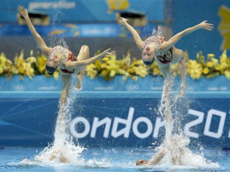 Members of the team of Russia are thrown up in the air during the women's team synchronized swimming technical routine at the Aquatics Centre in the Olympic Park during the 2012 Summer Olympics in London. (AP Photo/Michael Sohn)