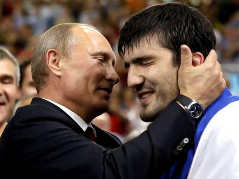 Russian President Vladimir Putin congratulates Tagir Khaibulaev of Russia after he beat Tuvshinbayar Naidan of Mongolia to win the gold medal during the men's 100-kg judo competition at the 2012 Summer Olympics, in London. (AP Photo/Paul Sancya)