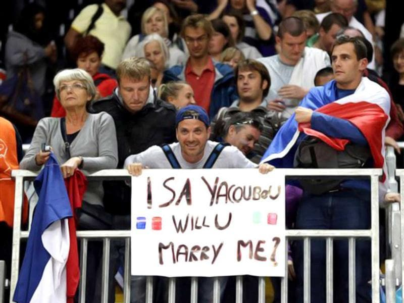 A man holds a sign with a marriage proposal for France women's basketball player Isabelle Yacoubou following a quarterfinal women's basketball game at the 2012 Summer Olympics, in London. (AP Photo/Eric Gay)