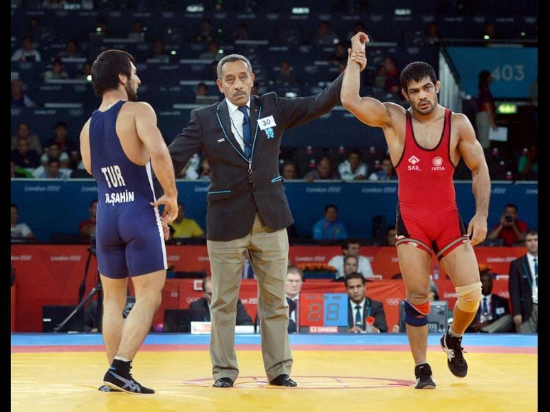 Sushil Kumar (in red) is declared winner as Turkey's Ramazan Sahin looks on, in their Men's 66kg Freestyle 1/8 Finals match at the Olympic Games in London. PTI/Manvender Vashist