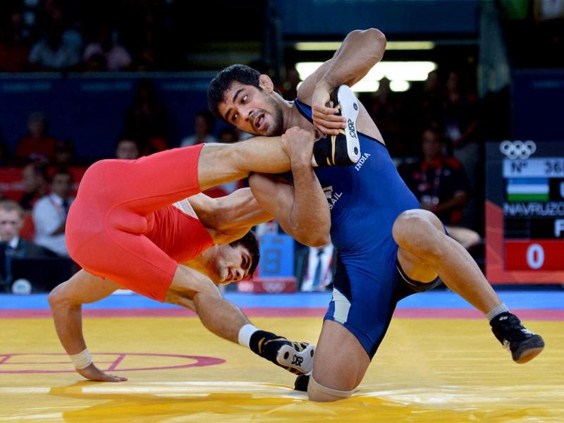 Sushil Kumar (in blue) wrestles with Uzbikistan lkhtiyor Navruzov in their Men's 66kg Freestyle Quaterfinal match at the Olympic Games in London. PTI/Manvender Vashist