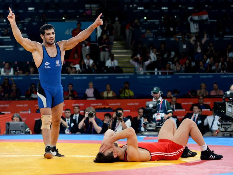 Sushil Kumar (in blue) celebrates his win against Kazakhistan's Akzhurek Tanatarov in their Men's 66kg Freestyle Semifinal match at the Olympic Games in London. PTI/Manvender Vashist