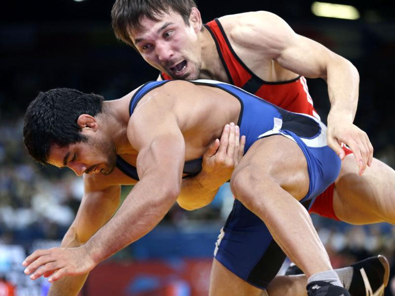 Akzhurek Tanatarov of Kazakhstan, competes with Sushil Kumar of India, (in blue) during their 66-kg freestyle wrestling match at the 2012 Summer Olympics, in London. AP/Paul Sancya