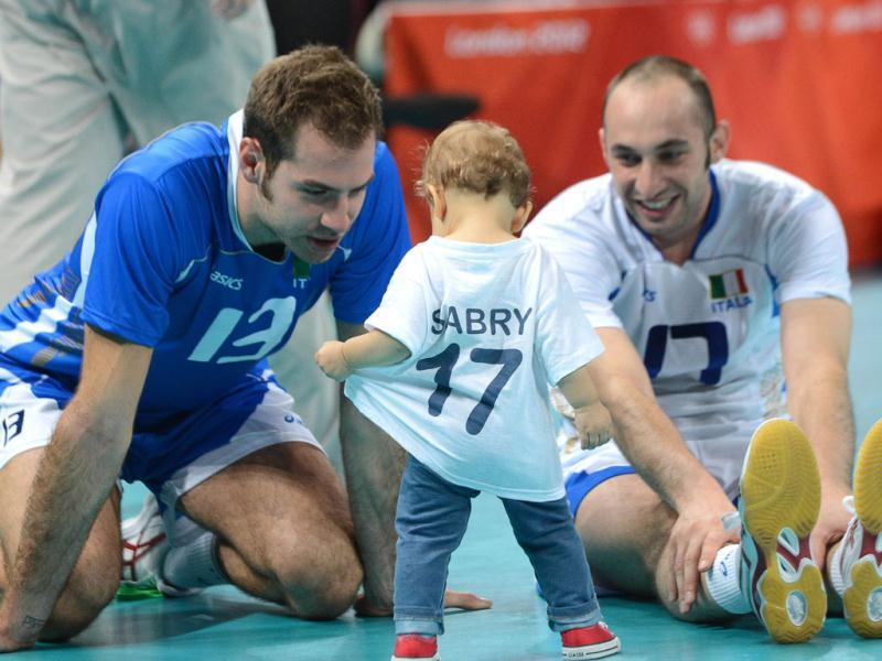 Italy's Andrea Giovi (R), with teammate Dragan Travica, plays with his daughter after defeating Bulgaria in the men's volleyball bronze medal match of the London 2012 Olympics Games against Bulgaria, in London. AFP Photo/Kirill Kudryavtsev