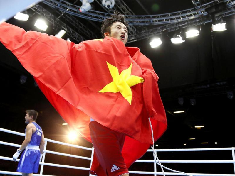 Shiming Zou of China waves the Chinese national flag following his gold medal points performance over Kaeo Pongprayoon of Thailand (L) in their Light Flyweight (49kg) boxing final of the 2012 London Olympic Games at the ExCel Arena in London. AFP/Jack Guez
