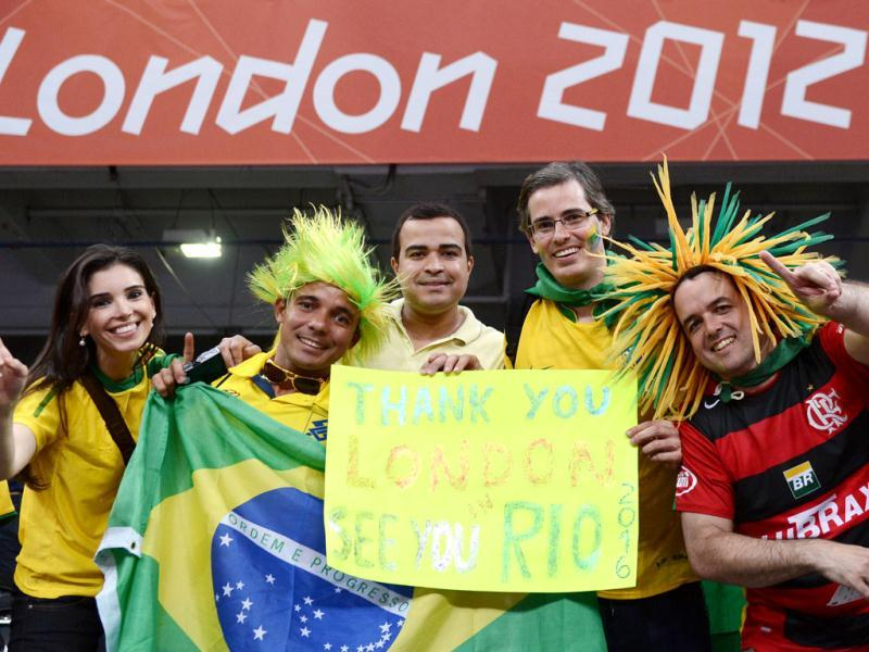 Fan pose for pictures with Games banner at an Olympic event in London. AFP Photo/Manan Vatsyayana