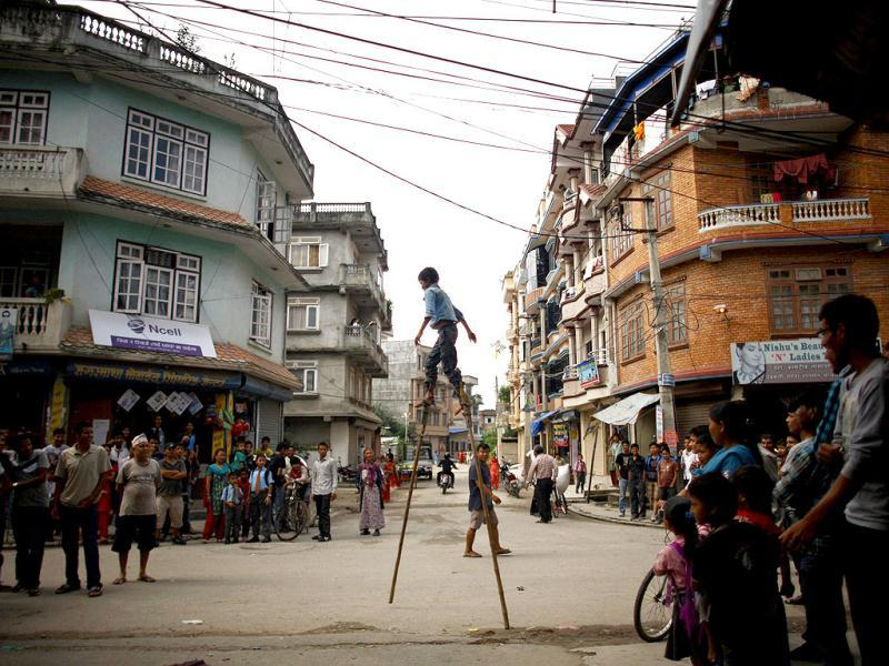 A boy balances on wooden poles as he performs tricks to earn his living on a street in Kathmandu. REUTERS/Navesh Chitrakar