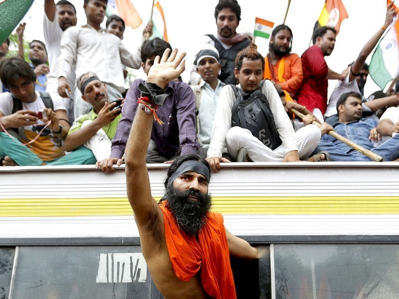 Indian yoga guru Baba Ramdev waves out of the window of a bus after he was detained with his supporters by policemen in New Delhi. AP/Saurabh Das