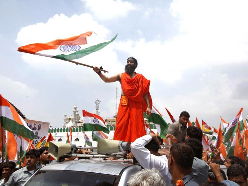 Yoga guru Baba Ramdev waves a national flag from atop a jeep as he along with his supporters march to Parliament to intensify an anti-corruption protest and press for a change of government in New Delhi. AP Photo/Rajesh Kumar Singh