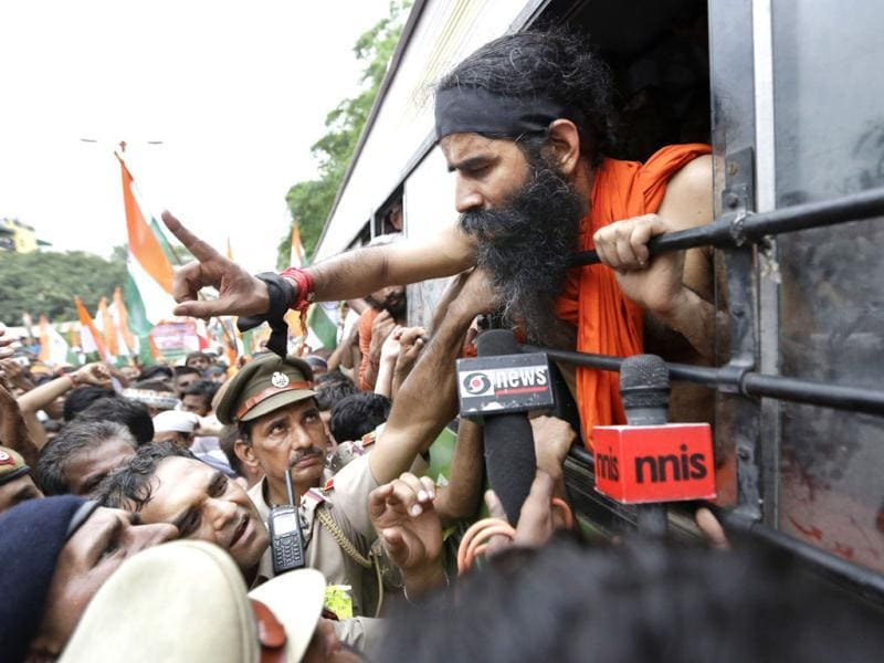 Yoga guru Baba Ramdev leans out of the window of a bus to talk to police officers after he was detained with his supporters in New Delhi. AP photo/Saurabh Das