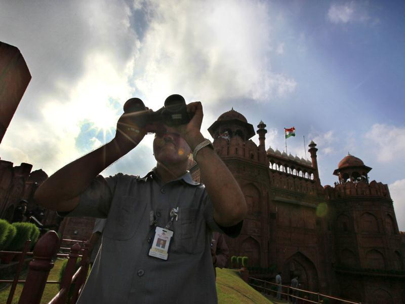 A security person uses a binocular to keep vigil Red Fort during the full dress rehearsal of Independence Day celebrations in New Delhi. HT photo/Raj K Raj