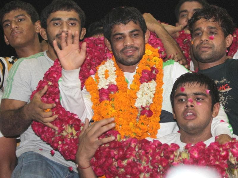 Wrestler Sushil Kumar, who won silver medal at London Olympics, is being greeted by his fans upon arrival at New Delhi's international airport. PTI/Kamal Kishore
