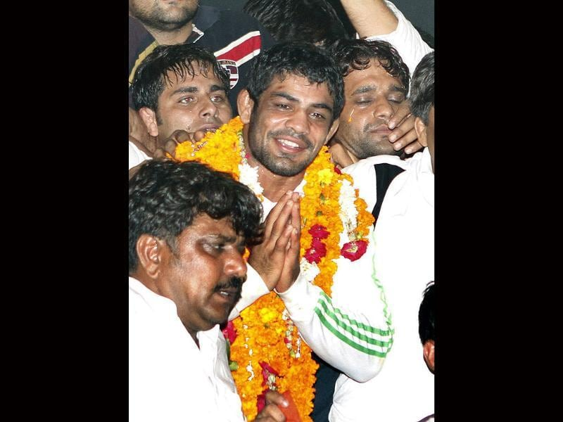 Wrestler Sushil Kumar, Olympics silver medalist in the men's 66kg freestyle event, gestures on his arrival at IGI airport in New Delhi. (Arijt Sen/HT Photos)