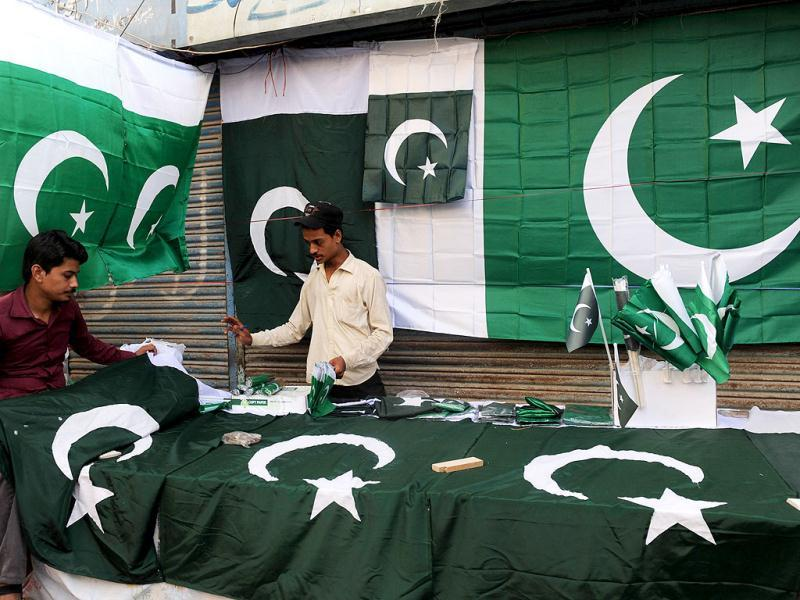 Pakistani vendors arrange national flags as they wait for customers at a roadside stall ahead of the country's Independence Day in Karachi. Pakistan will be celebrating its 65th anniversary of the country's independence from British rule on August 14. AFP PHOTO / RIZWAN TABASSUM