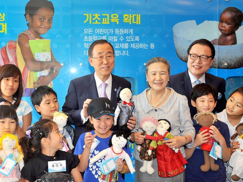 United Nations Secretary-General Ban Ki-Moon (C top) and his wife Yoo Soon-Taek (4th R) pose with a group of South Korean children as they visit the Korean Committee for Unicef in Seoul. Ban said he is seeking a way to ease tensions between North and South Korea, and promised more help to Pyongyang to recover from deadly floods, on August 13. AFP PHOTO / JUNG YEON-JE
