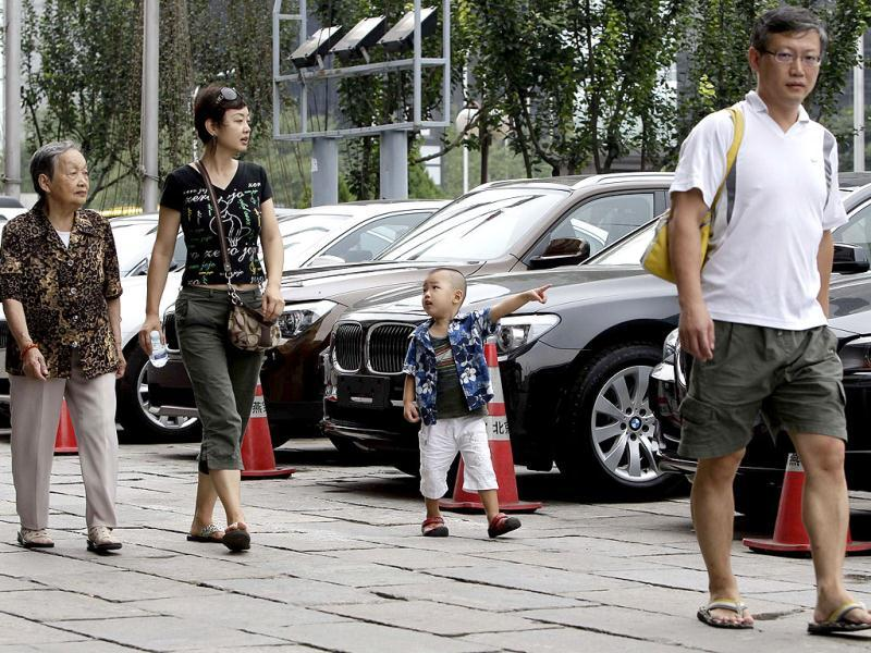 A family check BMW cars on sale outside its showroom in central Beijing. Chinese demand for automobiles slowed further in July from the previous two months as an economic slowdown and weak consumer confidence weighed on sales. REUTERS/Jason Lee