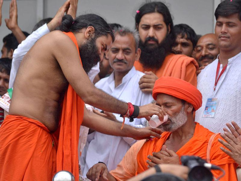 Baba Ramdev offers water to a supporter, who had fasted along with him, in New Delhi.
