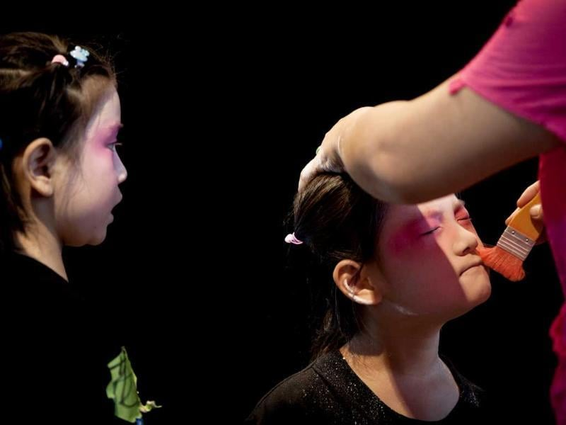 A girl is applied makeup before a training at Peking Opera summer camp organized by the Peking Opera House in Beijing, China. AP/Andy Wong