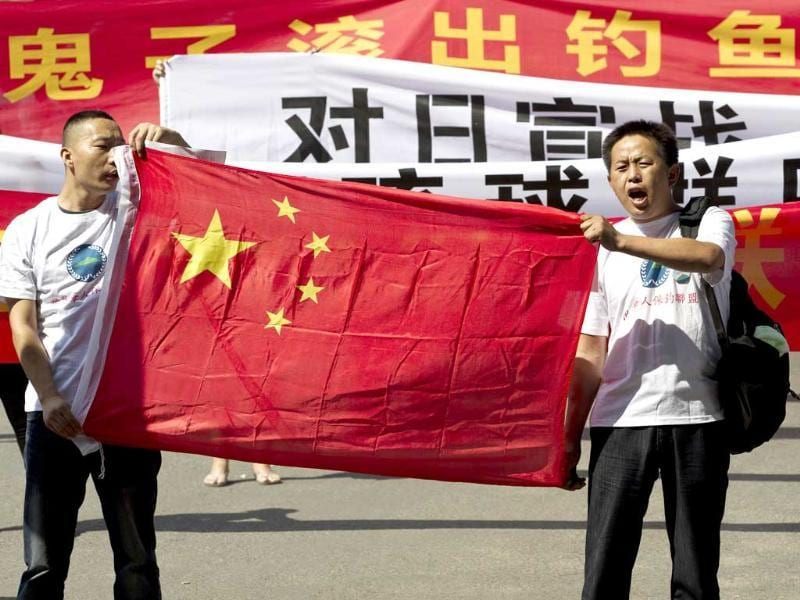 Chinese protesters hold a Chinese national flag and banners reading 'Declare war against Japan' and 'Japan get out of Diaoyu islands' during a protest outside the Japanese Embassy in Beijing. AP/Andy Wong