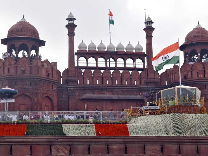 India's Prime Minister Manmohan Singh addresses the nation from a bullet-proof enclosure as Indian national flags flutter at the historic Red Fort during Independence Day celebrations in Delhi. (Reuters/B Mathur)