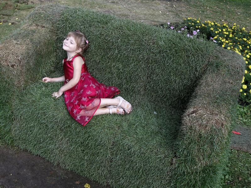 A girl lies on a couch that is covered with grass in a park in central Kiev. Reuters Photo