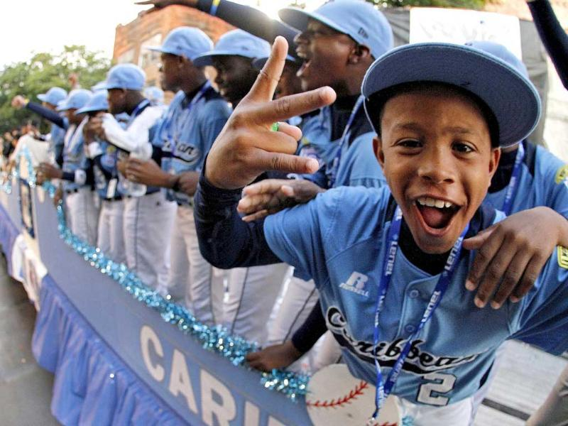 Members of the Little League team from Willemstad, Curacao, ride in the Little League Grand Slam Parade as it makes its way through downtown Williamsport. AP/Gene J Puskar