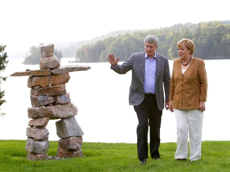 Canadian Prime Minister Stephen Harper chats with German chancellor Angela Merkel as they stand near an Inukshuk, a stone landmark, at the Prime Minister's official country residence at Harrington Lake, Quebec. AP/Fred Chartrand