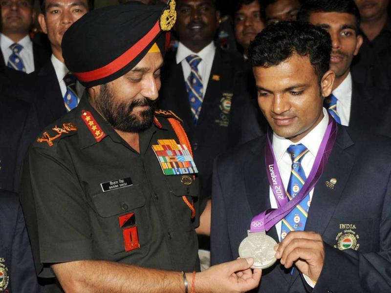 Army chief general Bikram Singh (L) poses with Olympic silver medal winner Vijay Kumar during an award function for Indian Army olympians at the army headquarters in New Delhi. AFP/Raveendran
