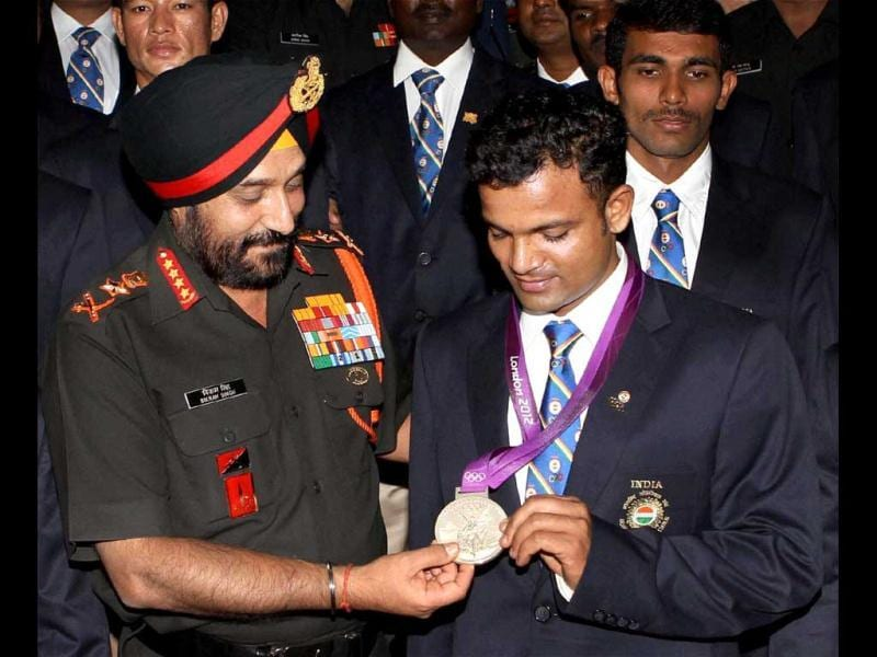 Olympic silver medallist shooter Vijay Kumar showing his medal to Chief of Army Staff Gen Bikram Singh during a function for felicitation of army personnel who participated in London Games 2012, in Defence Ministry in New Delhi. (PTI Photo by Shahbaz Khan)