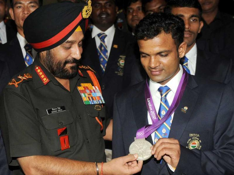 Army Chief General Bikram Singh (L) poses with Olympic silver medal winner Vijay Kumar during an award function for Indian Army olympians at the army headquarters in New Delhi. (AFP photo/Raveendran)