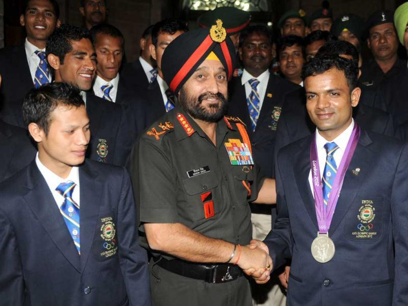 Army Chief General Bikram Singh shakes hands as he poses with Olympic silver medal winner Vijay Kumar during an award function for Indian Army olympians at the army headquarters in New Delhi. (AFP photo/Raveendran)