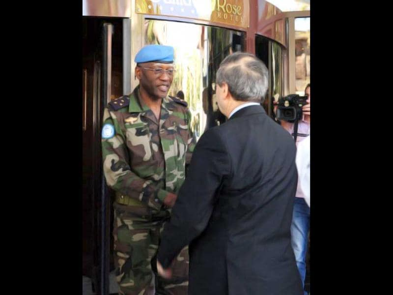 Syrian deputy foreign minister, Faisal Meqdad, shakes hands with Senegalese General Babacar Gaye, the head of the UN Supervision Mission in Syria, during a visit to his hotel following a bomb explosion in central Damascus near the hotel used by the UN observer mission in Syria.(AFP)