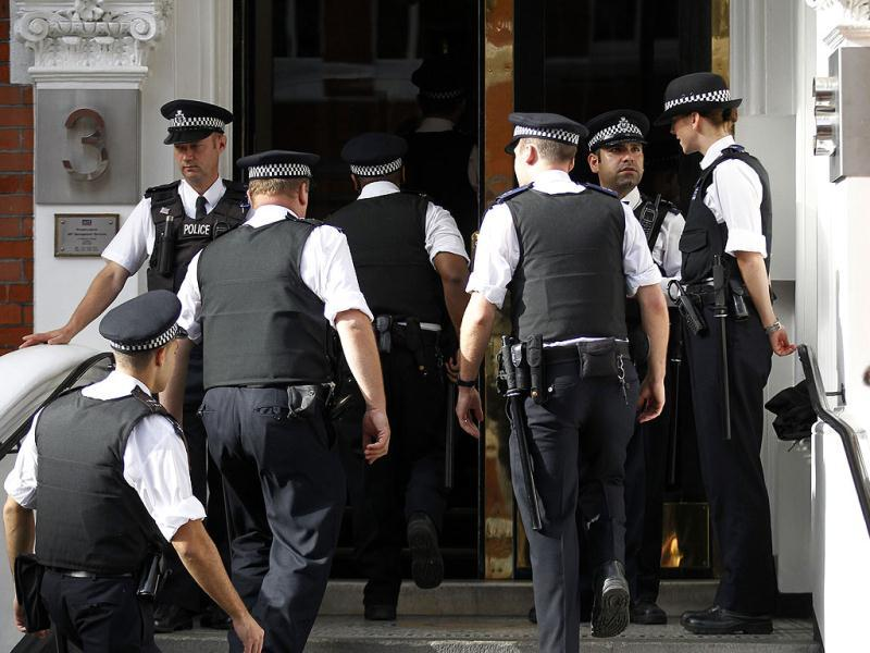 British police officers stand guard outside the Ecuadorian Embassy in central London. AP/Sang Tan