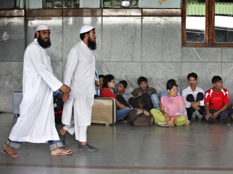 Muslims walk past people from India's northeastern states waiting to board trains to go back home, at a train station in Bangalore. AP Photo