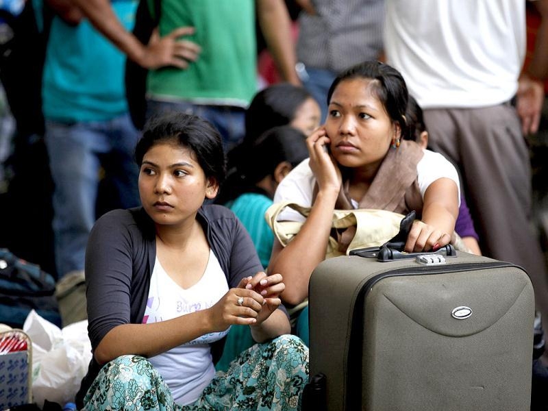 Women wait with their baggage to board trains home at a station in Bangalore. AP Photo