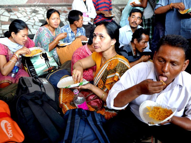 Northeastern residents eat while waiting on a train platform at a railway station in Bangalore. AFP Photo