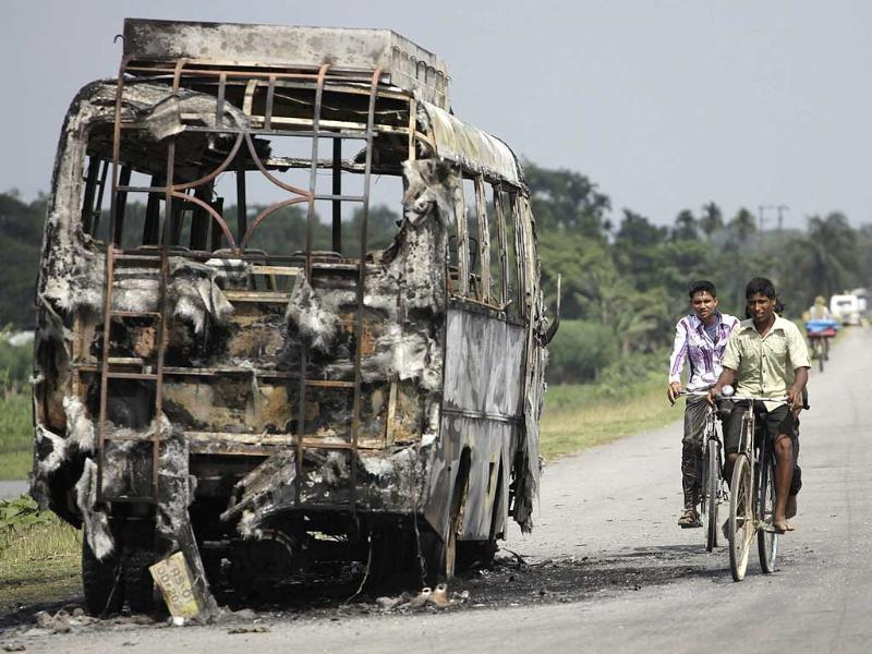 Two cyclists ride past a burnt vehicle in Rangiya, about 55 kilometers west of Guwahati, Assam. AP/Anupam Nath