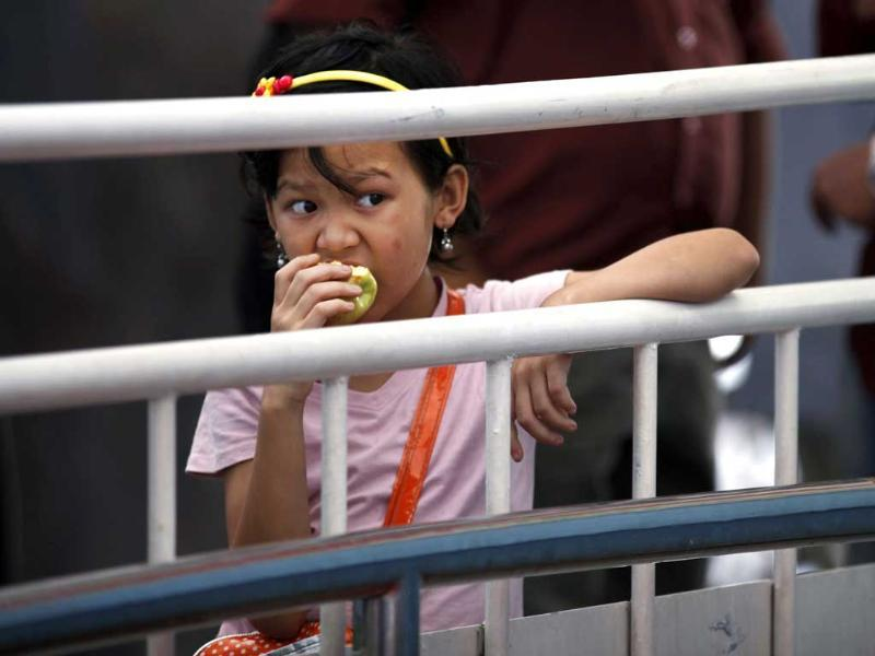 A girl from the northeast eats an apple as she waits to take a train home, at a station in Bangalore. AP/Aijaz Rahi