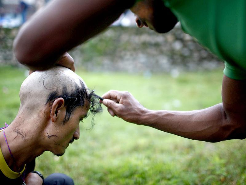 A man gets his head shaved before he offers a prayer in the name of his deceased father during Kuse Aunsi at Gokarneshwar temple in Katmandu. AP Photo
