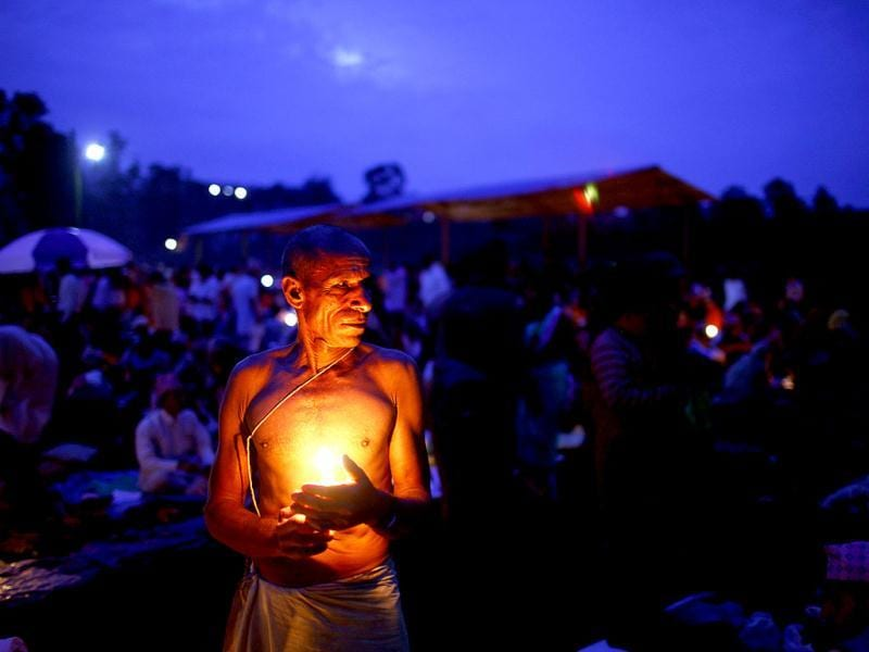 A man holds a candle while he gets ready to perform a ritual during Kuse Aunsi at Gokarneshwar temple in Katmandu. AP Photo