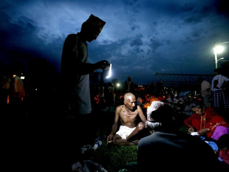 A man holds a light as other gets ready for a ritual during Kuse Aunsi festival at the Gokarneshwar temple in Katmandu. AP Photo