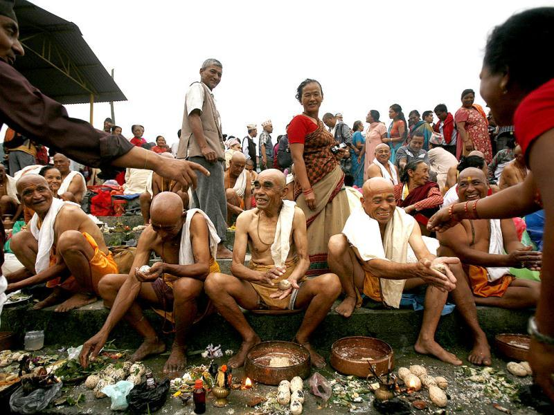 Nepalese men perform rituals during Kuse Aunsi or Nepalese Father's day at Gokarneshwar temple in Katmandu, Nepal. Kuse Aunsi is a festival of Nepal, where fathers living or dead are honored. Children with their fathers show their appreciation by giving presents and sweets and those whose fathers are deceased pay tributes at Gokarneshwar temple. AP Photo
