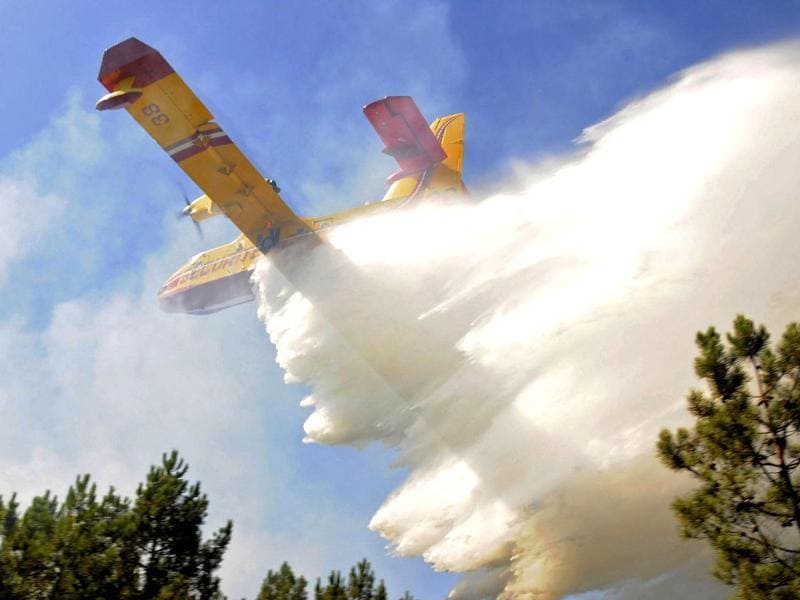 A firefighting tanker plane drops water above a forest fire near Lacanau, western France, Bordeaux. Reuters photo